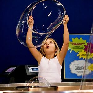 Girl making a large bubble at Sci-Quest