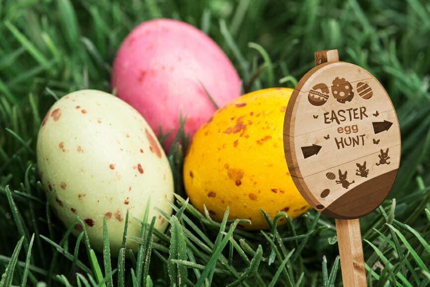 Easter egg hunt sign against three little easter eggs