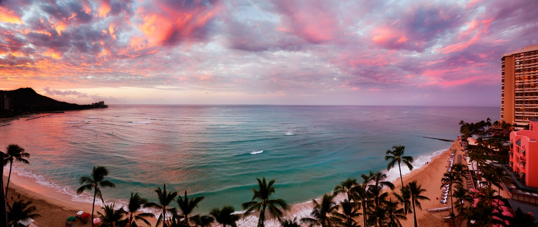 Waikiki Beach, Hawaii, as dawn lights up the clouds